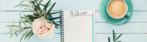 Morning coffee cup, notebook with to do list, pencil, eyeglasses