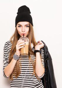 Millennial teenage girl drinking takeaway coffee, wearing modern