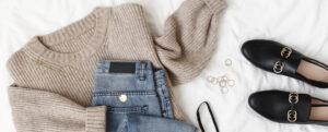 Blue jeans, beige knitted sweater, black lace bra, black loafers