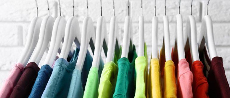 Shirts auf einem Kleiderbügel an einer Kleiderstange in unterschiedlichen Farben